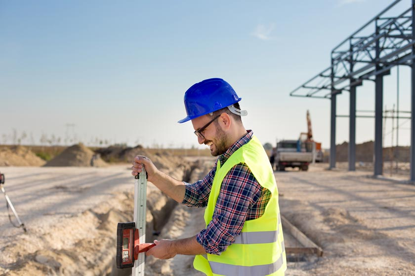 Mann mit Warnweste und Bauhelm auf einer Baustelle mit Laserempfänger